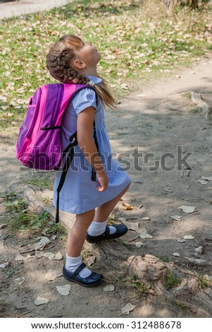 Preschool girl with braids dressed in school uniform gingham blue dress and black classic mary jane shoes going to school by foot and notice something interesting. Back to school. - stock photo