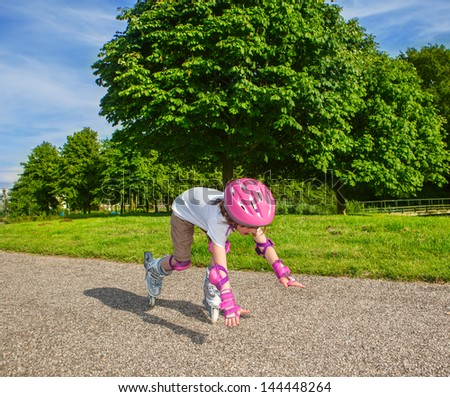 Preschool girl with inline roller skates on, falling down - stock photo