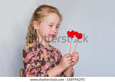 Preschool girl with strawberry blonde hairs and flowered dress who looks at two red hearts against the light grey background