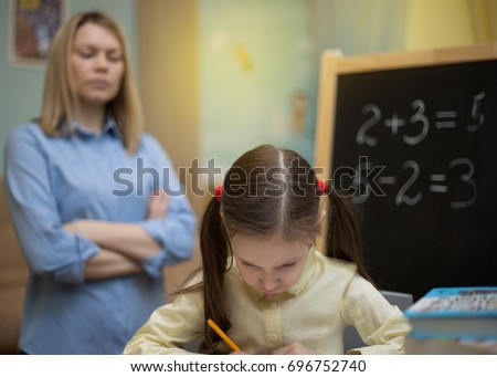 Preschool home education.  Beautiful young girl is teaching at home with exacting mother. Pretty young student.