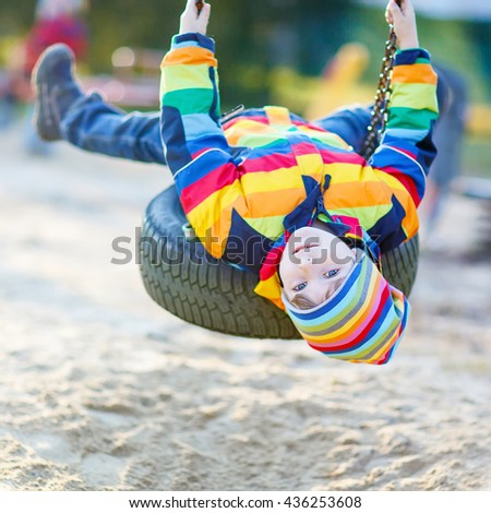 Preschool little kid boy having fun with chain swing on outdoor playground. child swinging on warm sunny spring or autumn day. Active leisure with kids. Boy wearing colorful clothes - stock photo