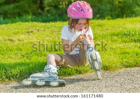 Preschool roller skate beginner looking at her bleeding knee. - stock photo
