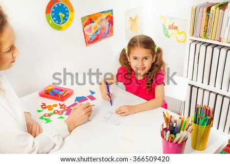 Preschool teacher helping pupil with class work - stock photo