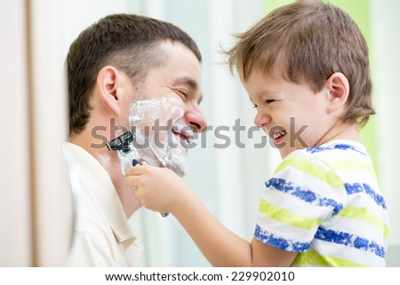 preschooler boy attempting to shave his dad - stock photo