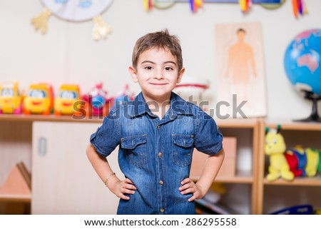 Preschooler boy posing at camera in classroom. - stock photo