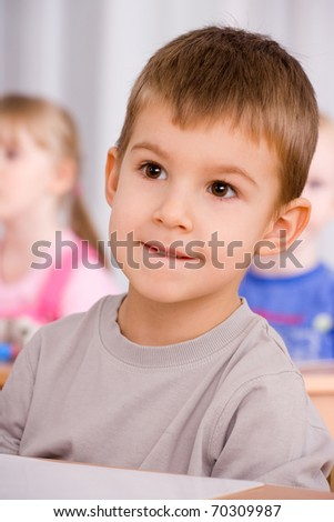 preschooler boy 4 years old listening a lesson in classroom - stock photo