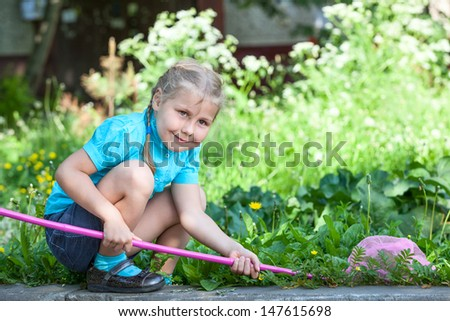 Preschooler Caucasian girl portrait when catching butterfly in the meadow - stock photo