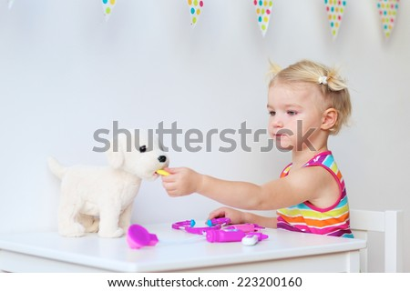 Preschooler child, cute blonde toddler girl, playing doctor role game and treating her puppy using pills and different medical tools - stock photo