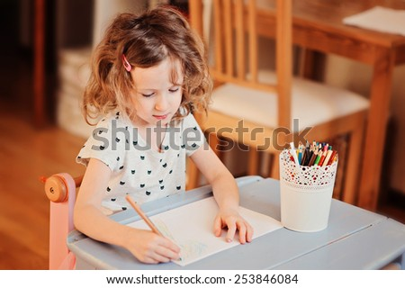preschooler child girl drawing with pencils at home  - stock photo