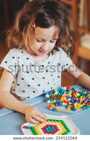 preschooler child girl plays with colorful mosaic at home - stock photo