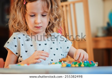 preschooler child girl plays with mosaic at home - stock photo