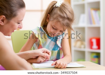 Preschooler Child Girl Reading with Mother In Nursery at Home - stock photo