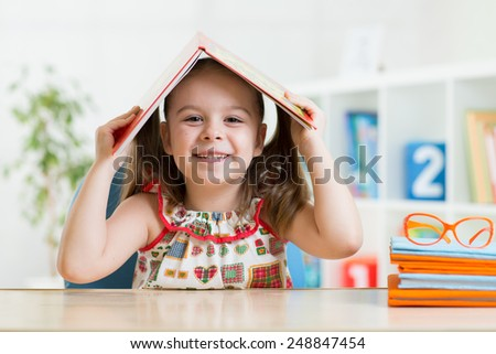 preschooler child girl with book over her head at home - stock photo