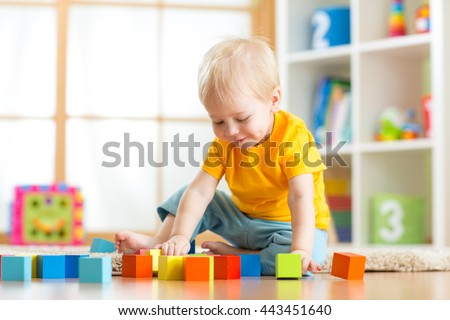 Preschooler child playing with colorful toy blocks. Kid playing with educational wooden toys at kindergarten or day care center. Toddler in nursery room. - stock photo