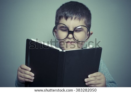 preschooler, dark-haired young student reading a funny book, reading and learning