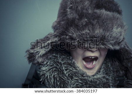 Preschooler, Funny child with fur hat and winter coat, cold concept and storm