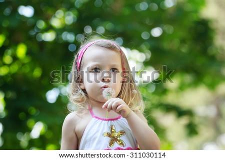 Preschooler girl is blowing on white Taraxacum officinale or common dandelion seeds in her arm - stock photo