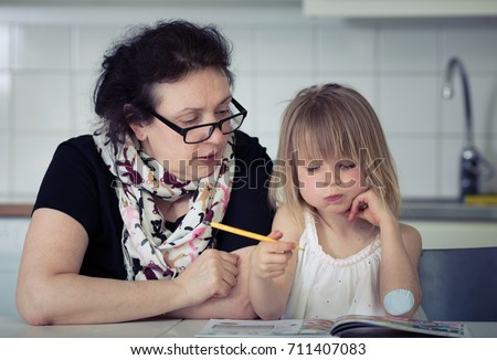 preschooler girl learning to read with help of teacher, grandma helping child to count and read after school at home. home education concept.