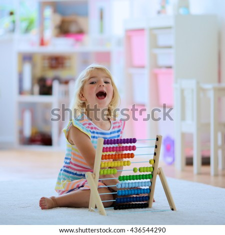 Preschooler girl learns to count. Cute child playing with abacus. Little girl having fun indoors at home, kindergarten or day care centre Educational concept for school kids. - stock photo
