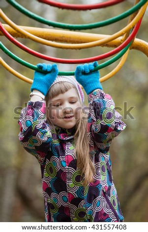 Preschooler girl playing on the playground - closeup shot - stock photo