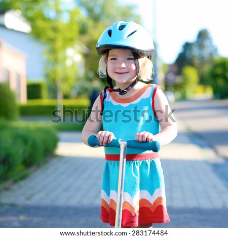 Preschooler girl riding scooter outdoors. Happy cute little child wearing blue safety helmet playing on the street learning to balance on kick board in the countryside - stock photo