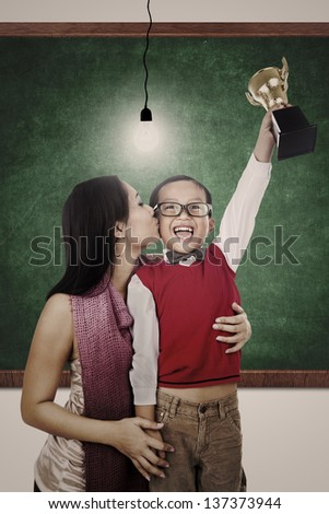 Preschooler holding a trophy in a classroom while his mum is kissing him