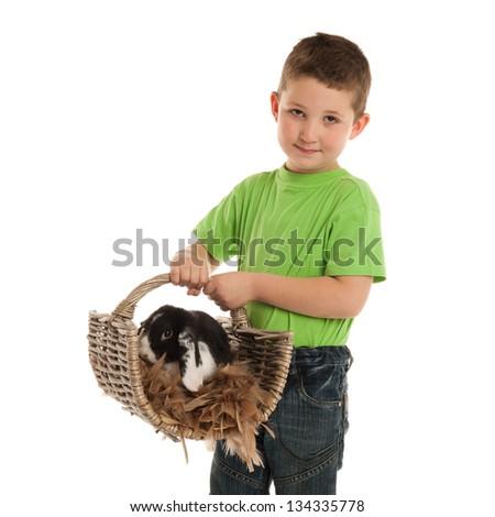 Preschooler is carrying his rabbit in a wicker basket - stock photo