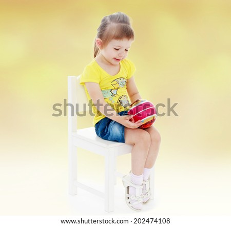 preschooler little girl sitting on a chair and holding the ball in front of him.passionate child for interesting occupation,active lifestyle,happiness concept,carefree childhood concept. - stock photo