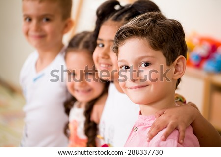 Preschooler posing at camera in classroom. - stock photo