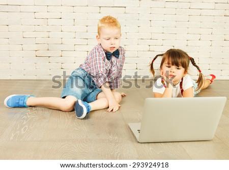 Preschoolers with laptop on the floor - stock photo