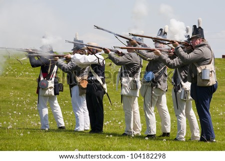 PRESCOTT, ONTARIO - MAY 21: American soldiers group firing their flintlock rifles during a reenactment of the War of 1812, on May 21, 2012 at Fort Wellington, Prescott, Ontario. - stock photo