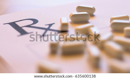 Prescribing, overprescribing prescription pills concept with blank RX form and falling tablets, close up in natural light, shallow DOF.
