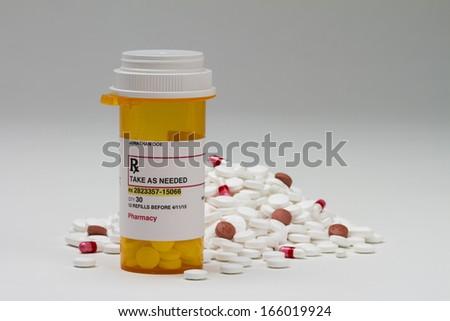 Prescription bottle next to pile of pills, horizontal - stock photo