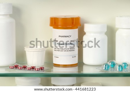 Prescription bottle on medicine cabinet shelf. Label is fictitious and created by photographer.