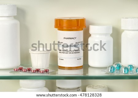 Prescription bottle on medicine cabinet shelf. Labels are fictitious and  created by the photographer.