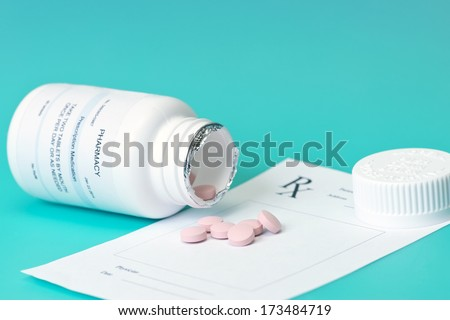 Prescription bottle, pink pills, and pad on blue background.