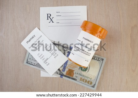Prescription bottle, receipt and blank script on desktop.