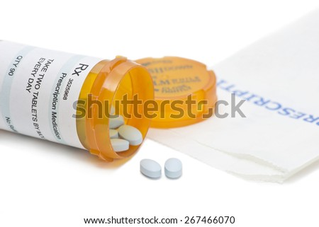 Prescription bottle with blue pills and retail pharmacy bag.  Label and all information contained therein is fictitious. - stock photo