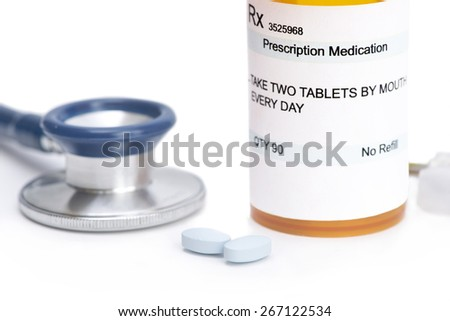 Prescription bottle with pills and stethoscope on white. Label and all information contained therein is fictitious. - stock photo
