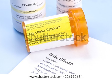 Prescription bottle with warning label and drug side effects print out. - stock photo