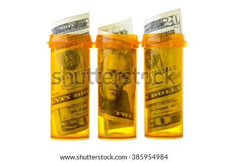 Prescription drug bottles with twenty dollar bills inside, isolated on white - stock photo