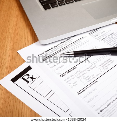 Prescription form with  pen and laptop computer