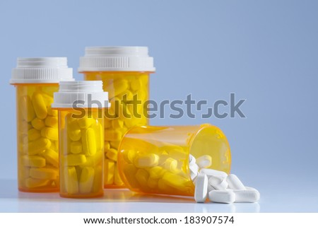 Prescription medication spilling from an open bottle. Caplets or pills in the opening of a medicine bottle with other standing bottles in the background.  - stock photo
