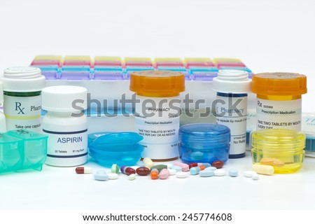 Prescription medications, pills, and daily med organizer boxes. - stock photo