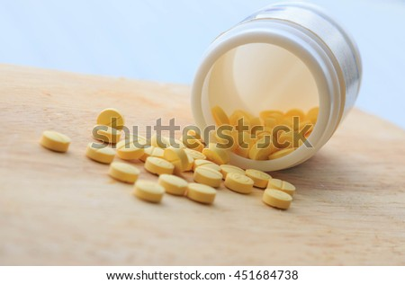 Prescription pill bottle spilling pills on to surface isolated. - stock photo