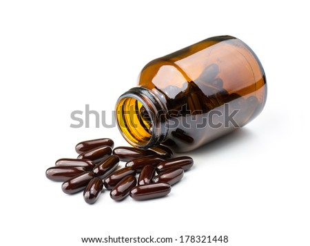Prescription pill bottle spilling pills on to surface isolated on a white background. - stock photo