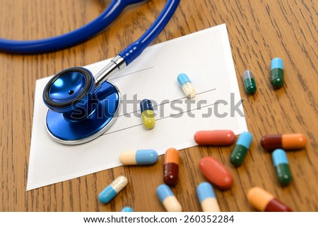 prescription with colorful pills and stethoscope on wooden ground - stock photo