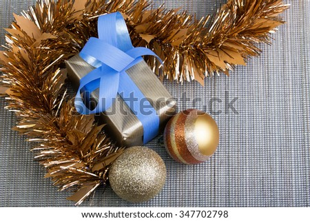 present and christmas balls in gold, red as background gray for copy space / gift and christmas balls in silver tablecloth background