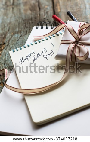 Present box and spring snowball flowers for Mothers Day on rustic background