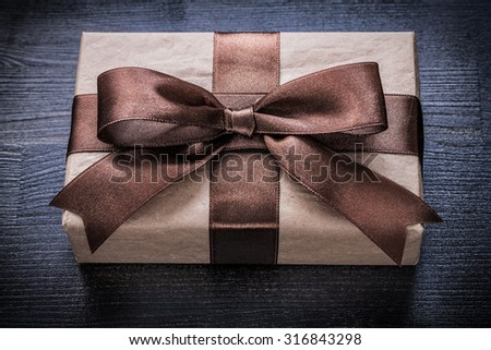 Present box-container in wrapping paper on vintage wooden board.